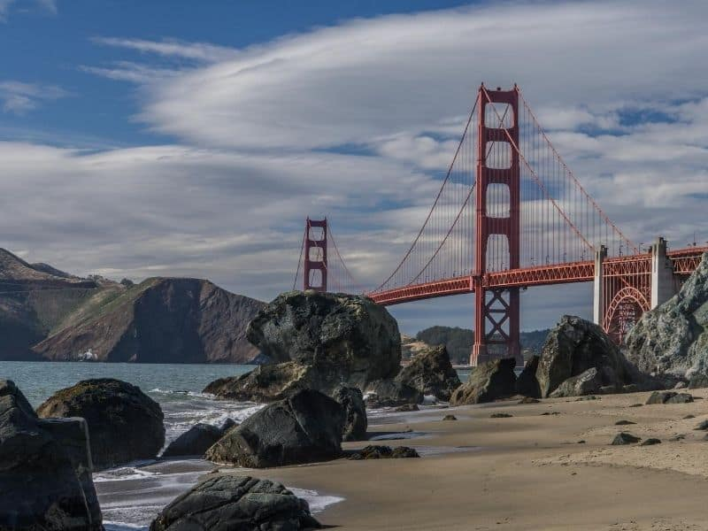 View of the Golden Gate bridge with lots of rocks on a beach and marin headlands in the distance on a partly cloudy day