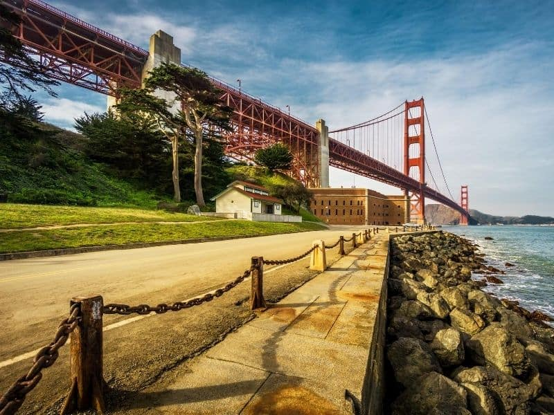 Red golden gate bridge with two buildings in the foreground on a boardwalk with rocky path