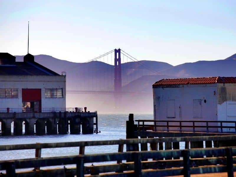 View of the San Francisco piers on a foggy day with the Golden Gate bridge appearing out of a fog, like in the San Francisco quotes you'll find on this page.