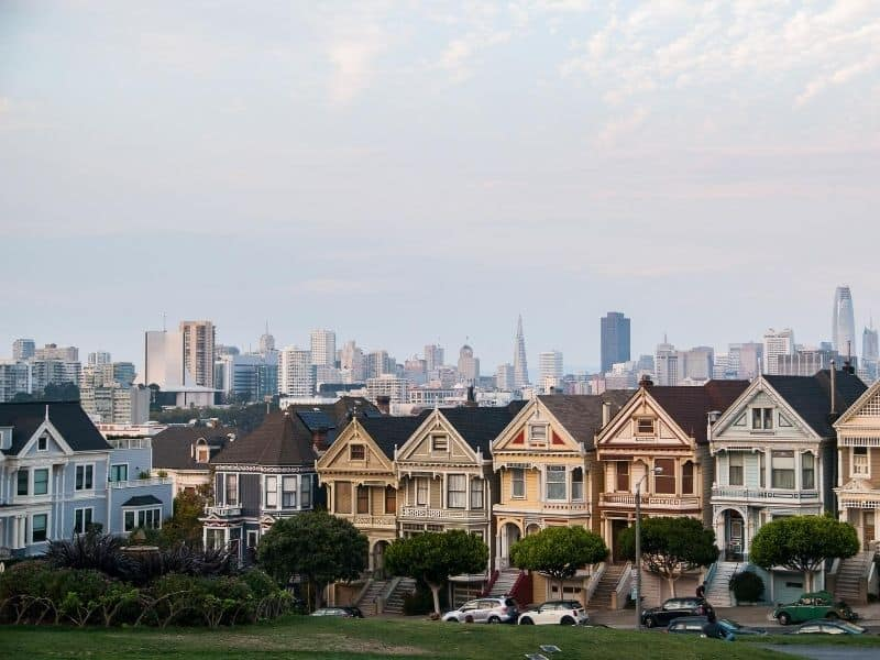 Row of pastel-painted Victorian houses going down a hill, with a patch of grass in front of it, with the San Francisco skyline behind it on a partly cloudy day.