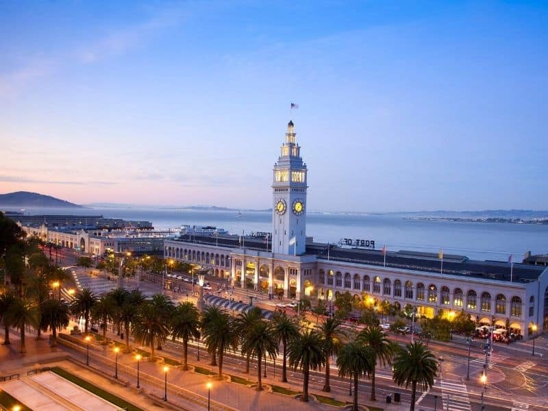 A view of the famous San Francisco ferry building, lit up at night with a clocktower and a small flag, with the Embarcadero around it.