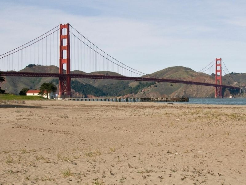 Sandy beach with bay water and red suspension bridge with hills in the distance.