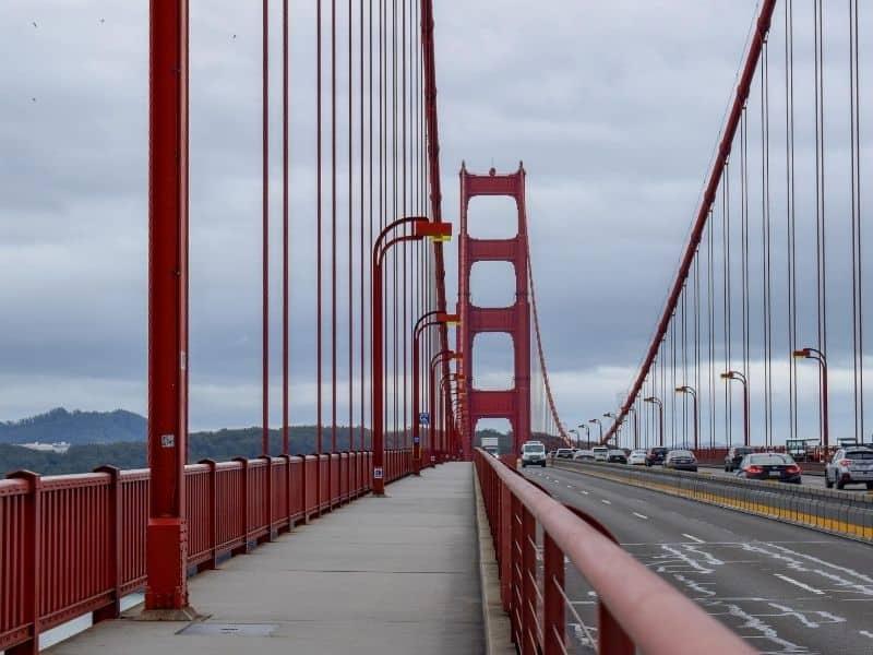 Pedestrian walking path on the Golden Gate Bridge, a red suspension bridge, on a foggy San Francisco date.