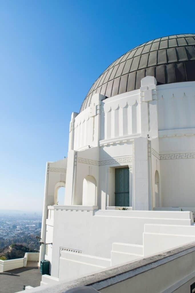 White building with gray dome roof, the Griffith Observatory in Los Angeles, with view of city in distant background below.