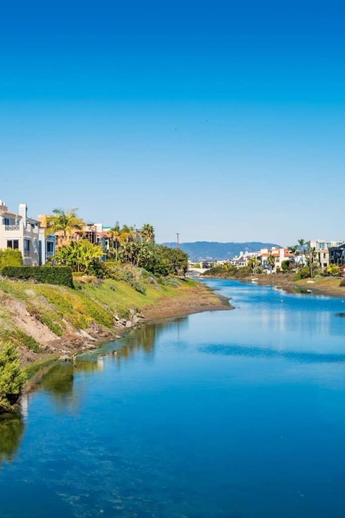 View of artificial canal with houses built one each side and hills in the distance in Venice Beach, California
