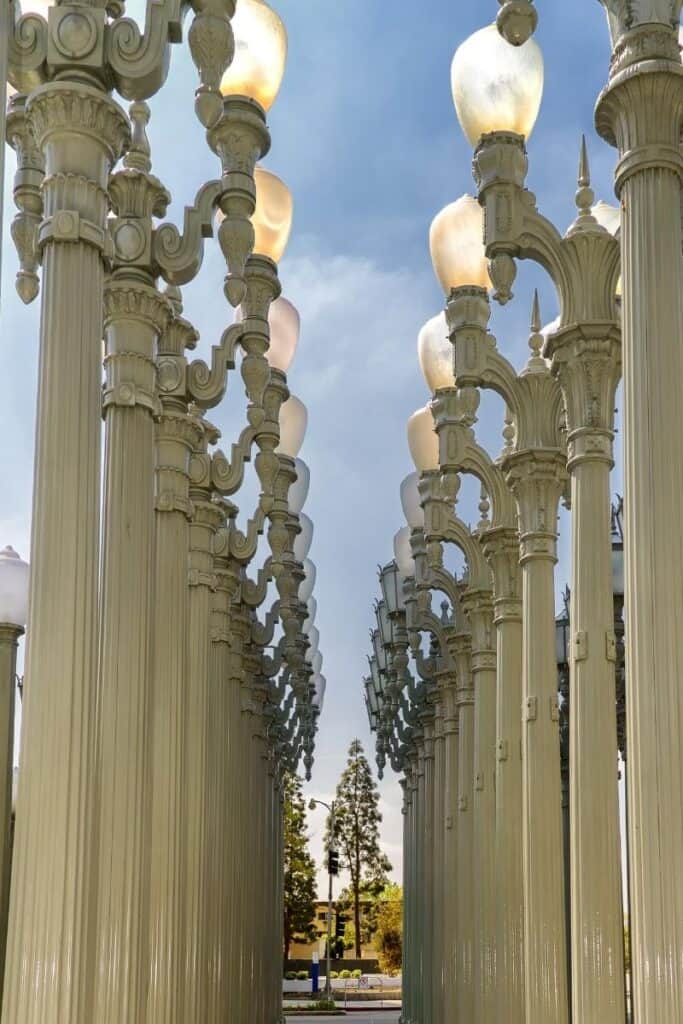 Tall white vintage lampposts standing in rows as part of an urban art installation at LACMA
