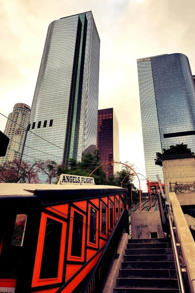 "View of historic red and black ""Angel's Flight"" tramway with giant skyscrapers in background."