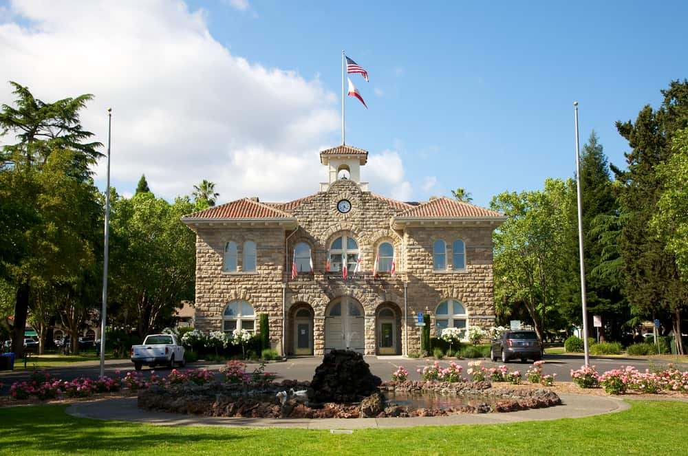 Symmetrical stone building with trees and plaza that is Sonoma's Town Hall