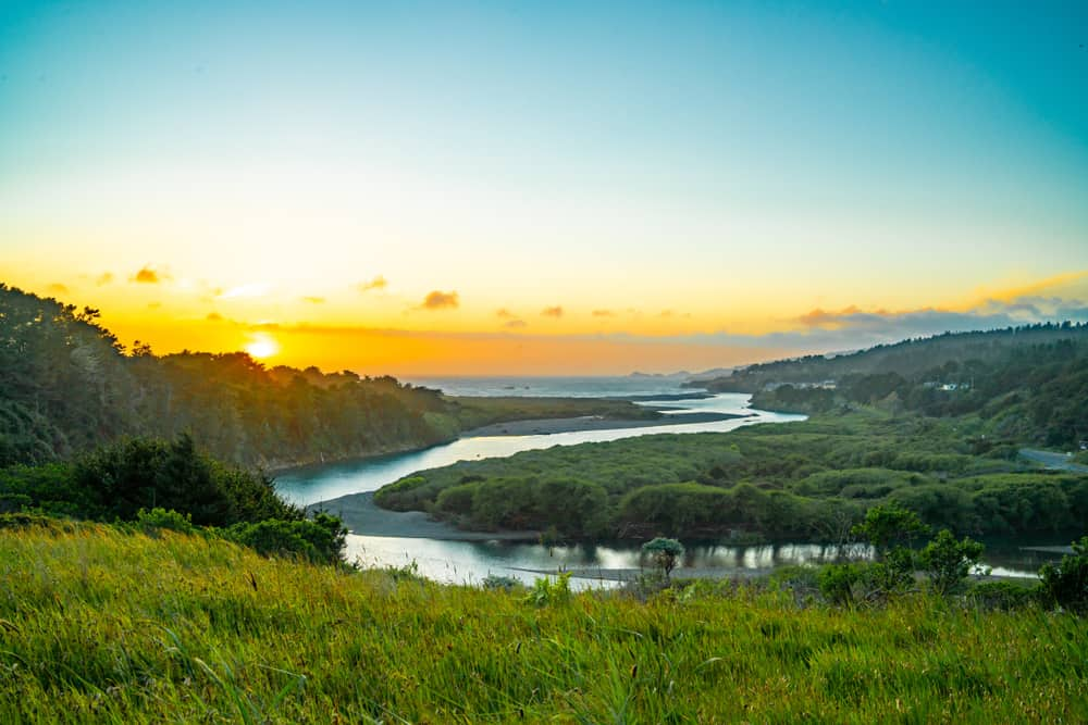 View from mountain of twists of Gualala river emptying into the Pacific Ocean with sunset tones of blue and orange