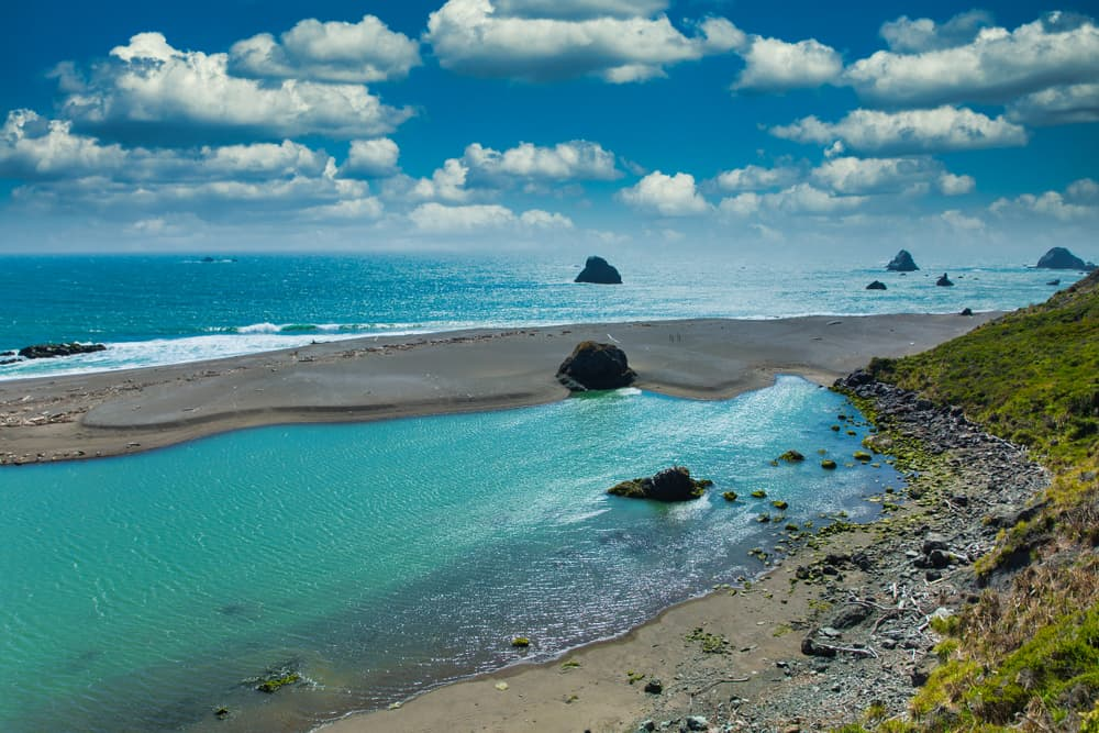 Brilliant turquoise river meeting sea with sand bar in between in Jenner