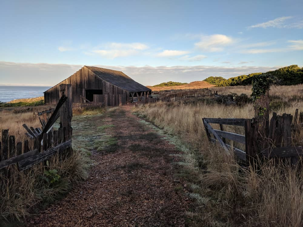 Old barn on trail with sea in background and dry grass