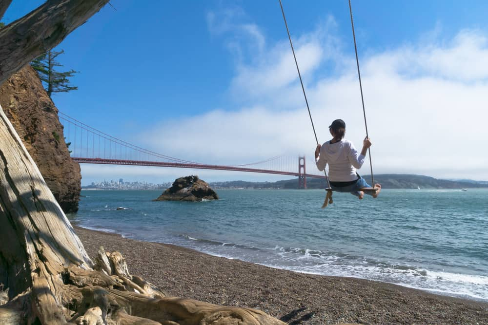 Woman with black or brown hair swinging on wooden swing hanging from a tree on a beach in San Francisco Bay with a view of the red bridge, Golden Gate Bridge, in the background. This is actually a Northern California campground!