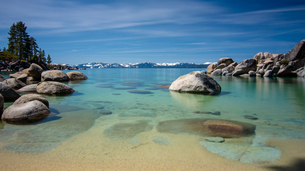 blue transparent water, rocky shore and snow on tops of background mountains on a blue sky day with few clouds
