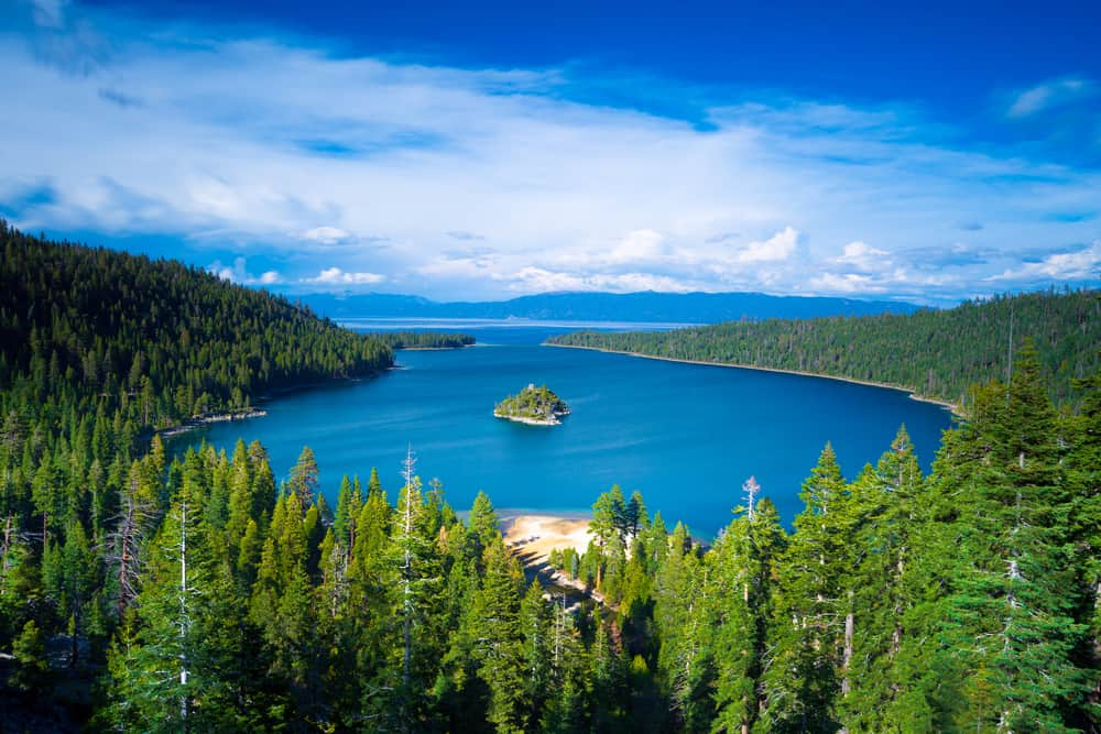 The view of Emerald Bay from above - lots of pine trees surrounding a turquoise blue lake with a small island in the center.