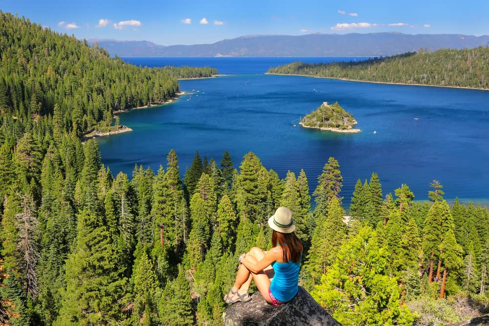 A female redheaded hiker in Tahoe who has hiked to a stunning view of Emerald Bay, where you can see cerulean blue water surrounded by pine trees and one tiny lone island in the water.