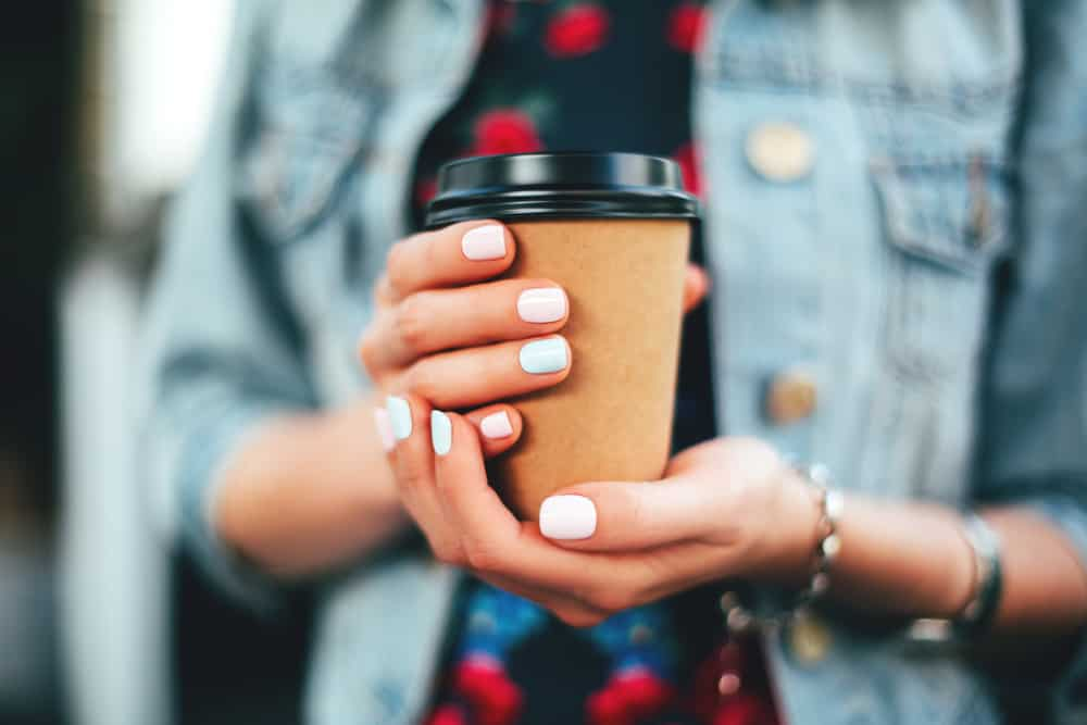a woman's hands with painted nails in pastel colors holding a to-go cup of coffee, wearing a denim jacket and dress