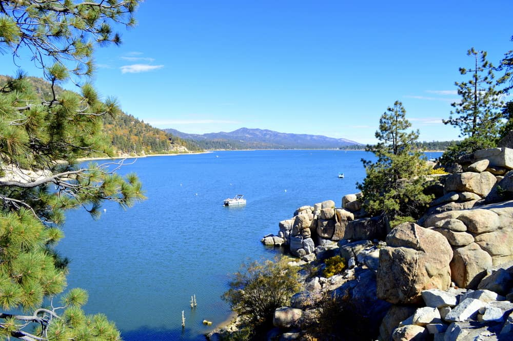A large brilliant blue lake, surrounded by rocks and trees, with one boat out in the middle of the lake.