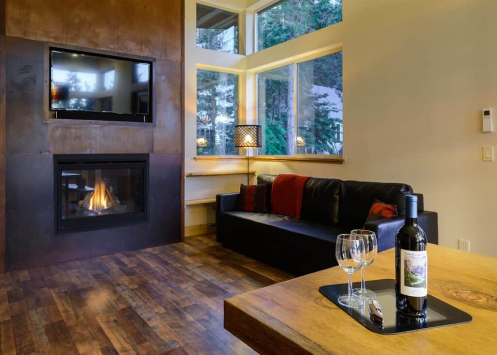 Bottle of wine with two glasses with leather sofa and fireplace