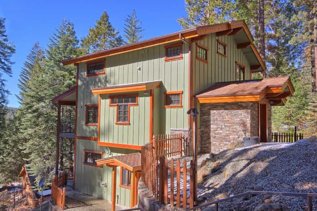 Green multi-story cabin with pine trees