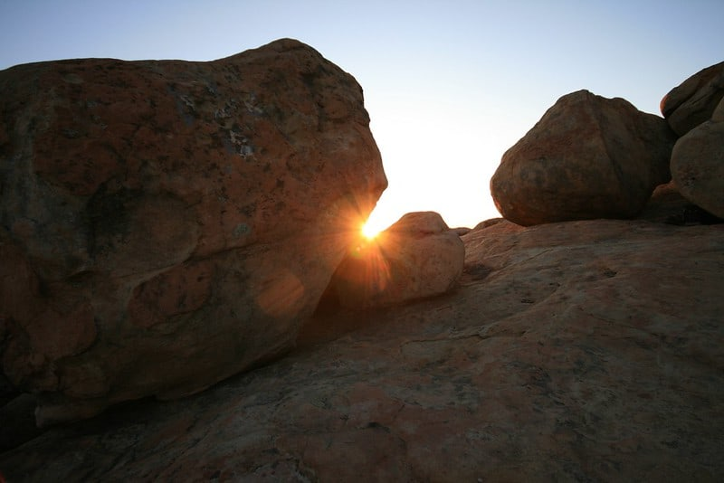 Sunburst of the setting sun going down between rocks, one of which is shaped like a lizard's head