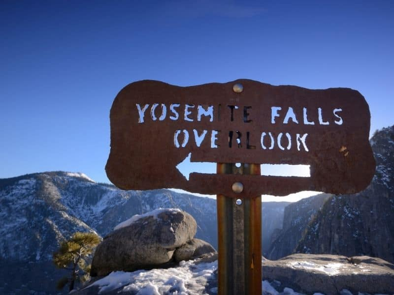 "Sign that reads ""Yosemite Falls Overlook"" with snow in background showing it is winter in Yosemite."
