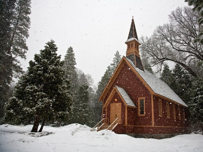 Famous Yosemite chapel (a small reddish-brown church) in the lightly falling snow with trees covered in snow and white sky.