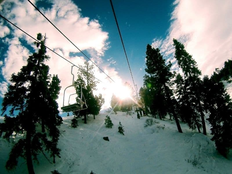 Sunburst on a partly cloudy day of Big Bear in winter chair lifts for skiing and snowboarding