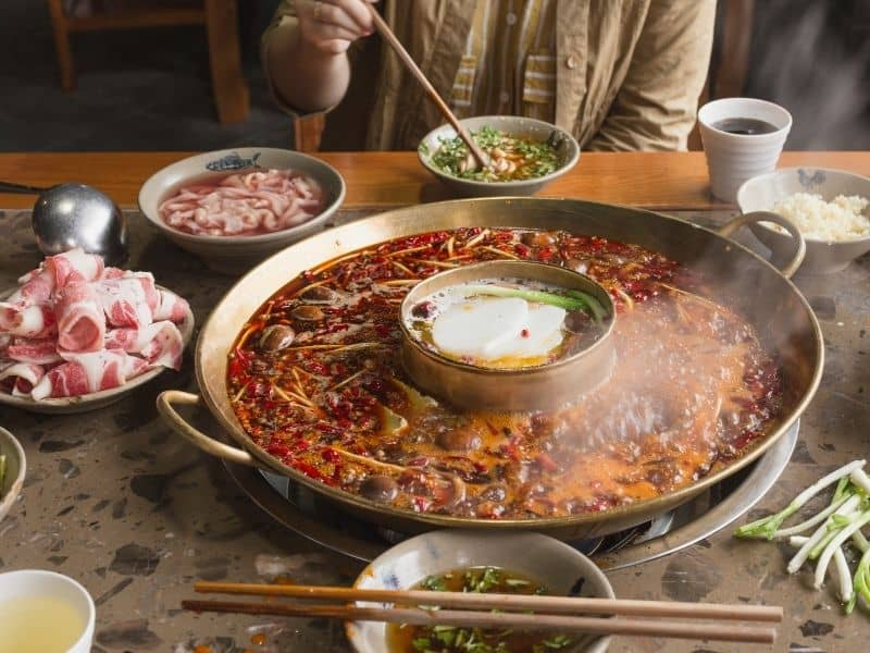 Eating Sichuan hot pot with large soup bowl raw meat and vegetables for dipping into soup and eating.