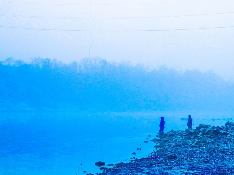 Cloudy foggy morning with two people in dark clothing fishing on side of lake