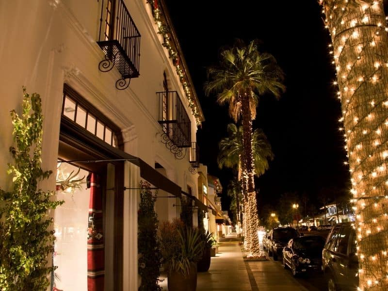 A main street in Palm Springs California with Christmas lights strung up on palm trees
