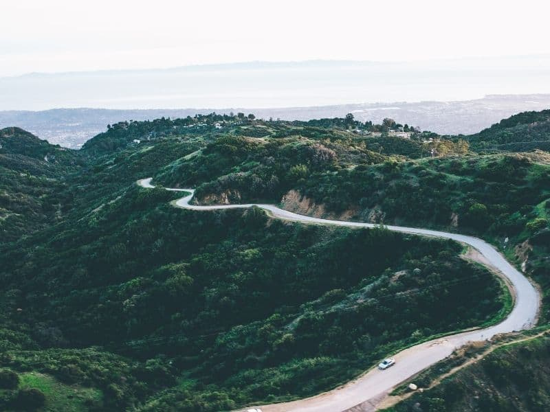 An aerial view of a mountain road in Santa Barbara with the Pacific Ocean in the background far away.
