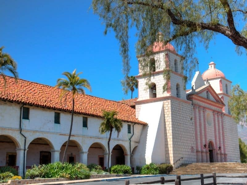 The historic Santa Barbara Mission done in the Franciscan architecture style: a Spanish-looking white and red-bricked church.