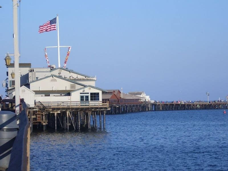 An afternoon view of the pier in Santa Barbara with old wooden structures and an American flag.