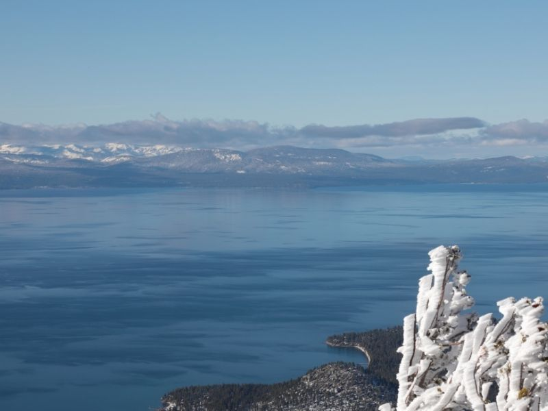 A winter in Lake Tahoe view from Heavenly Mountain accessed via a gondola ride: blue, blue lake, and white snow detail.