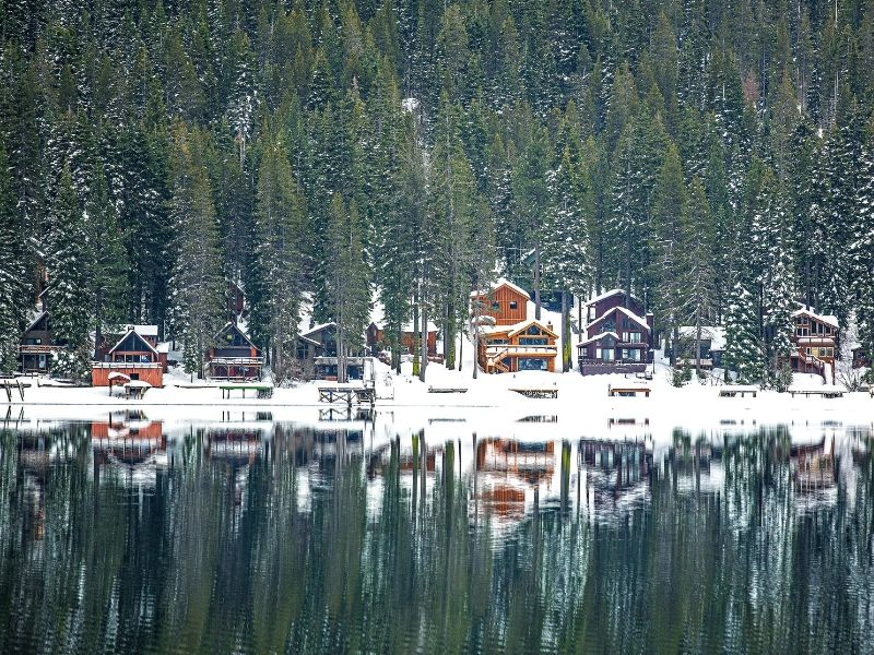 A view of the snow-covered cabins on Donner Lake in winter reflecting in the water with pine trees in the background.