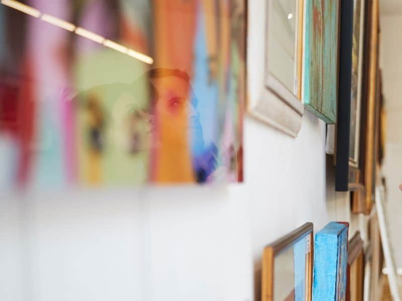 A close-up photo of gallery detail with couples face reflected in a piece of art looking at the pictures.