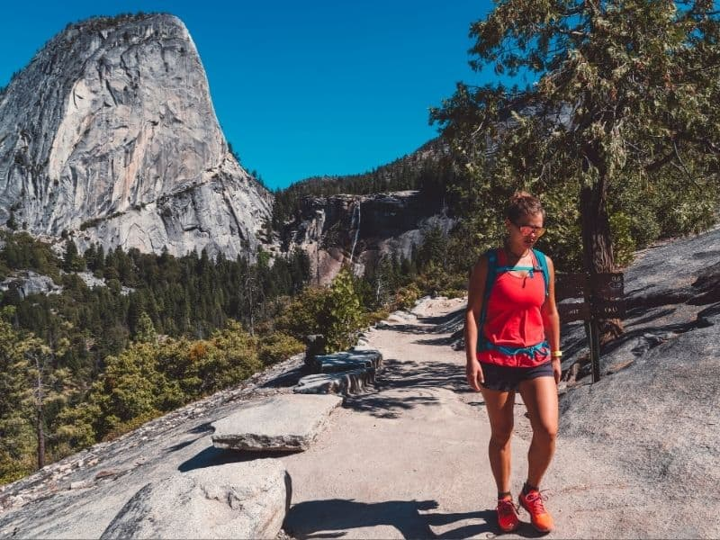 Woman in red shirt and sunglasses and shorts with turquoise backpack and red shoes on a Yosemite trail.