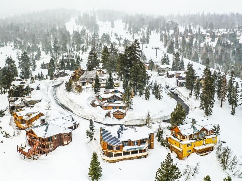 Aerial view of Mammoth Lakes in winter with lots of cabins and hotels covered in snow.