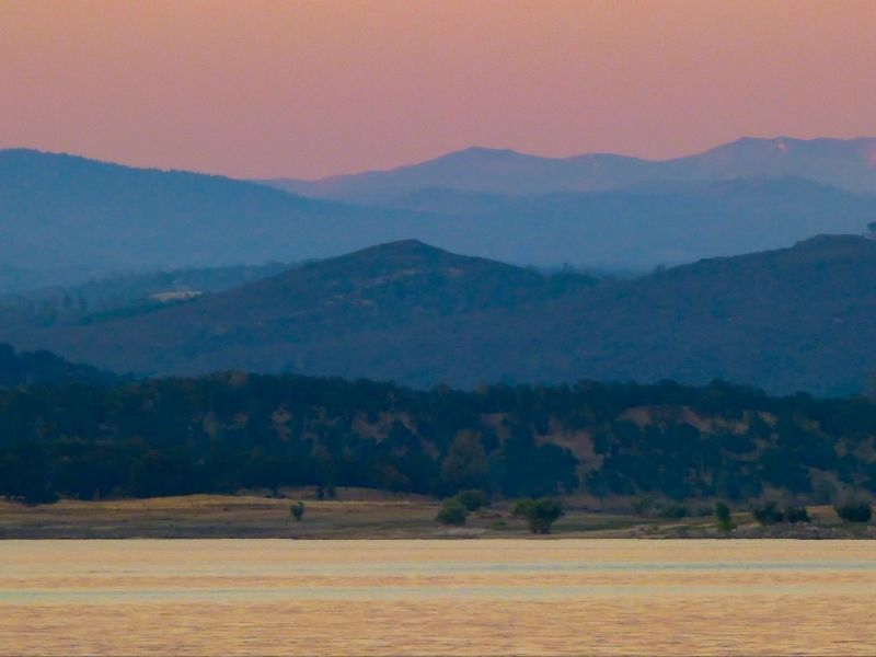 Grassy plain in foreground with mountains in background and pink sky at sunset.