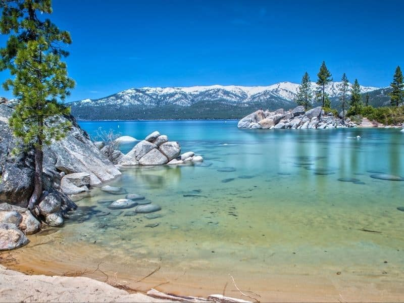 Caribbean-blue water ranging from light green to deep blue in Tahoe campground in Northern California, with snow on mountains in background and pine trees and rocks on lake shore.