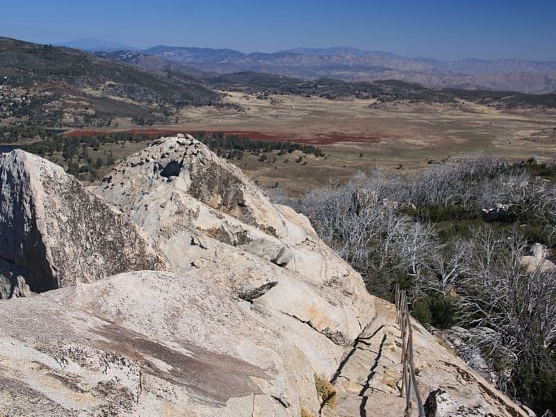 Large rock in foreground with view from higher elevation of the plains and trees below.