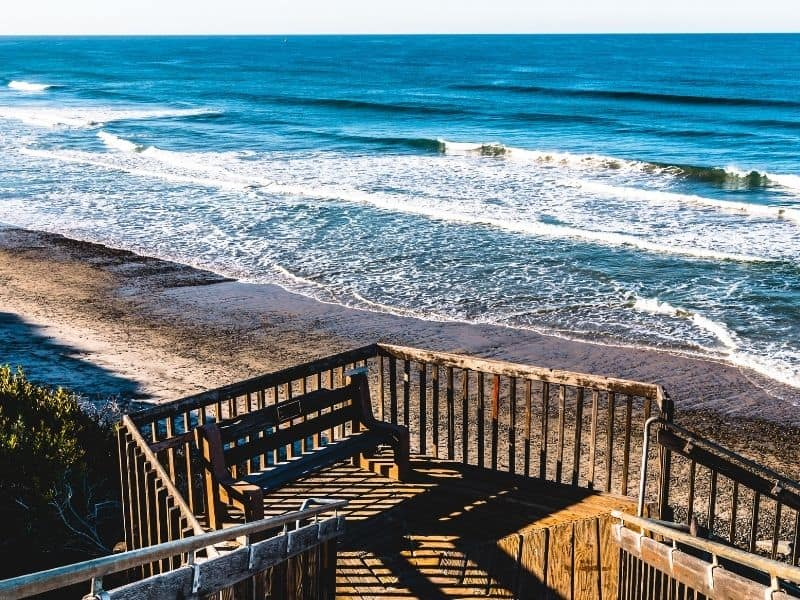 Wooden curving staircase leading to beach with cerulean blue ocean waves lapping calming on shore.