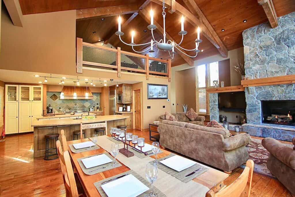 Interior photo of long dining table, fireplace with sofas, inviting cabin concept.