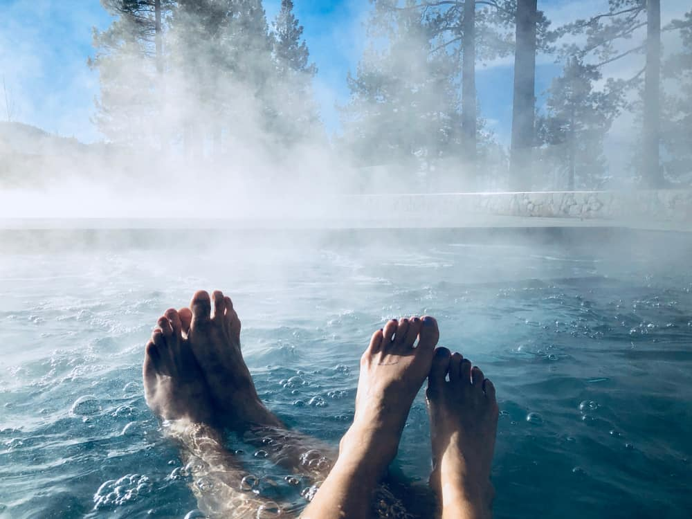Two couples showing their feet while enjoying a hot tub pool with steam in Lake Tahoe in winter