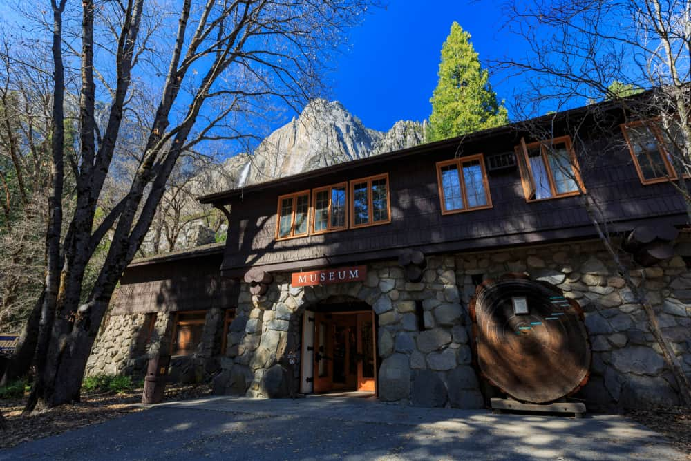 "Stone building that says ""museum"" located in Yosemite national park with view of waterfall peeking behind the museum."