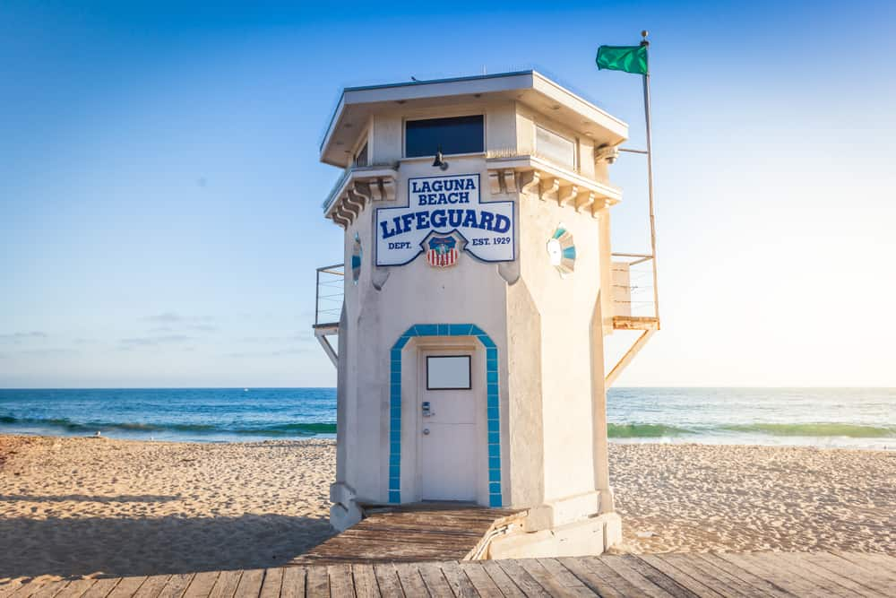 Laguna Beach lifeguard tower on an empty beach with a small flag, on a beach with blue water behind it, a popular weekend getaway from LA