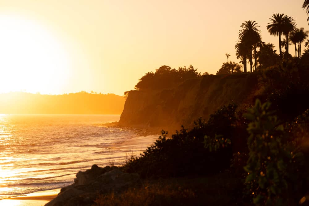 A beautiful orange and pink sunset on the cliffs of Butterfly Beach, the perfect end to a weekend in Santa Barbara itinerary.