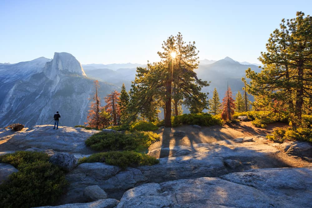 Sunburst through a tree with rocks in shadow with one man standing on cliff edge with Half Dome granite peak in background.