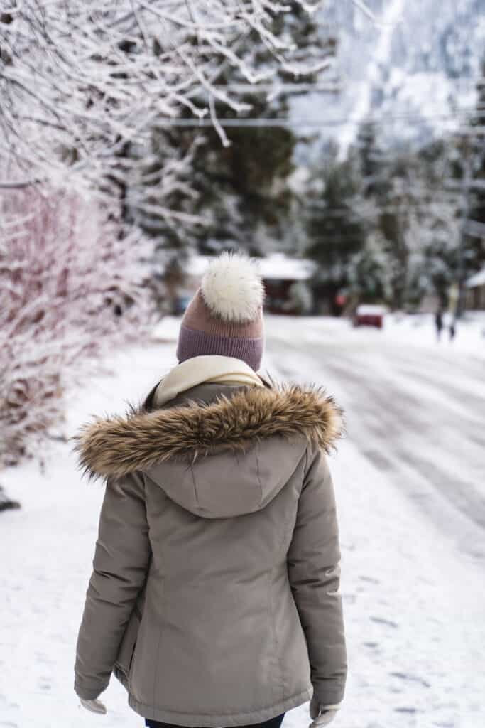 A photo of a woman wearing a pink hat and beige parka from behind on a street in Lake Tahoe in winter