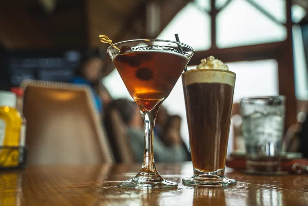 A low-angle photo of two cocktails: one is a martini with olives and the other looks to be a hot chocolate-inspired cocktail.